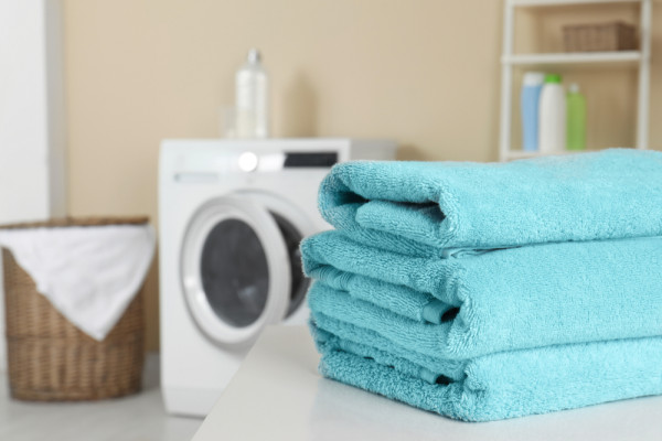 dry blue towels infront of a tumble dryer
